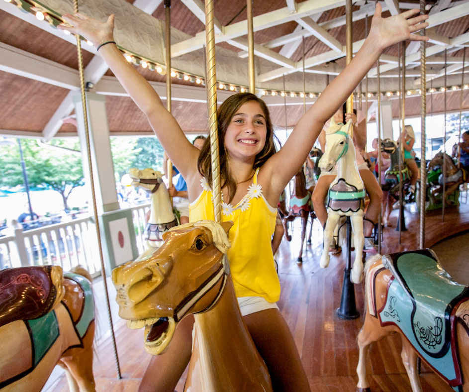 Young girl smiling with hands up riding the carousel