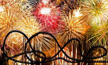 Roller coaster silhouette with fireworks in the background