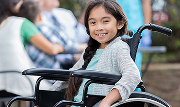 young girl sitting in wheelchair and smiling