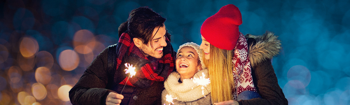 Family of 3 bundled up and smiling at each other with sparklers in hand