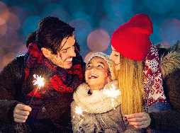 a mother and father smiling with their daughter holding a sparkler at Holiday Lights