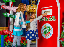 Two children putting letters to Santa in a Santa mailbox at Holiday Lights