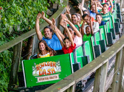 Boulder Dash roller coaster train coming through the woods with people screaming