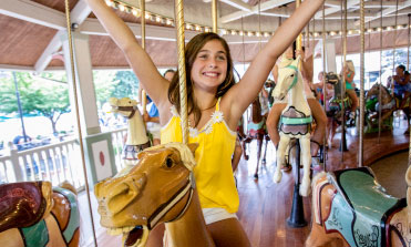 Girl on carousel with arms up