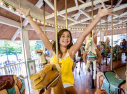 Girl on carousel with arms up smiling