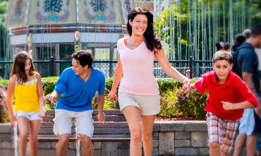 Boy holding moms hand and running toward attraction, both smiling