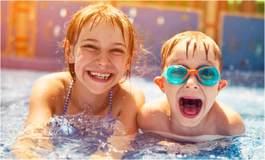 Boy and girl smiling at the camera in a pool.