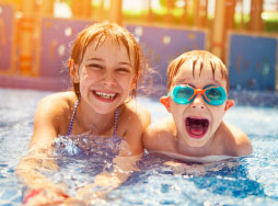Two kids in the wave pool smiling at the camera