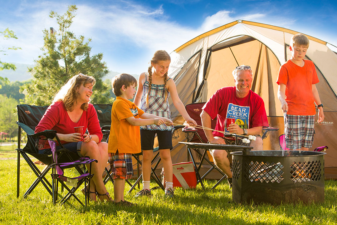 Family by tent roasting marshmallows