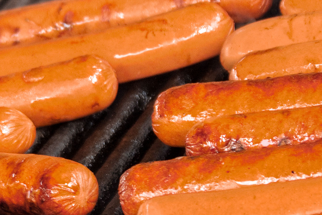 Closeup of hot dogs being grilled