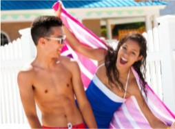 Young man and young woman with her arms spread out on towel smiling at each other