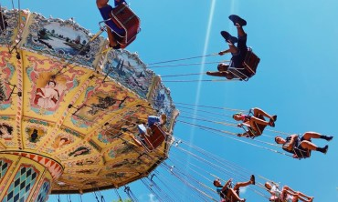 Wave Swinger ride from below with people in the seats against a blue sky