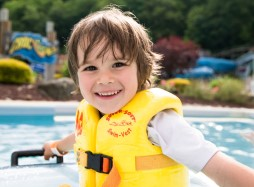 Young boy smiling in Croc O Nile with a yellow life jacket