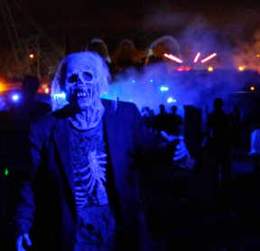 zombie in ripped suit walking in the haunted graveyard with fog and spooky lights